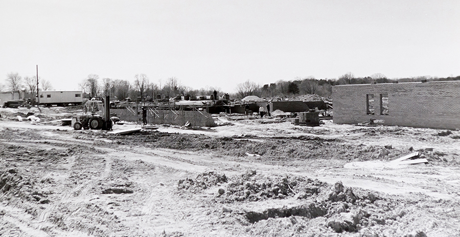 Black and white photograph taken during the early stages of construction of Fort Hunt Elementary School. The brick exterior walls are being built, and are approximately chest high. Construction materials, a trailer, a large fork lift, and several workmen are visible in the distance.