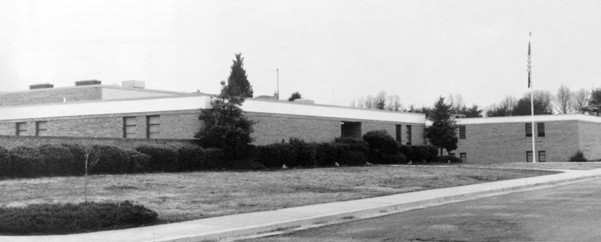 Black and white photograph of the front exterior of Fort Hunt Elementary School from our 1988 to 1989 yearbook. The building is pictured in its original configuration before any additions had been constructed.