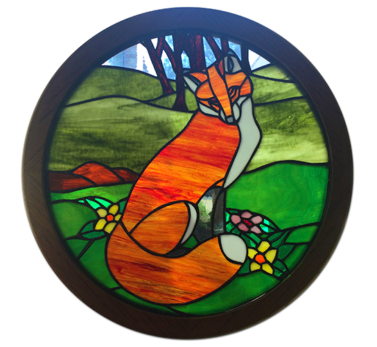 Photograph of the stained glass art depicting Fort Hunt's fox mascot. An orange, red, and white colored fox is pictured against a green background of rolling hills and trees. The piece is circular in shape and is held in a dark wooden frame.