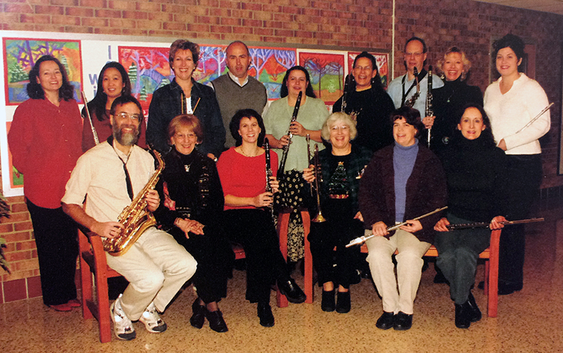 Color photograph from Fort Hunt's 1999 to 2000 yearbook showing a group of school staff known as the Senior Band. 15 staff members are pictured, most of whom are holding musical instruments. Flutes, clarinets, saxophones, and a trumpet are visible.